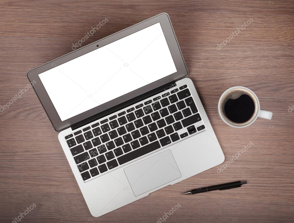 Laptop and coffee cup on wood table