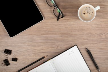 Tablet, notepad, glasses and coffee cup