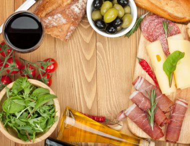 Red wine with cheese, olives, tomatoes, prosciutto, bread and spices