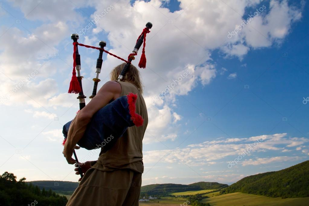 Bagpiper playing on a hill
