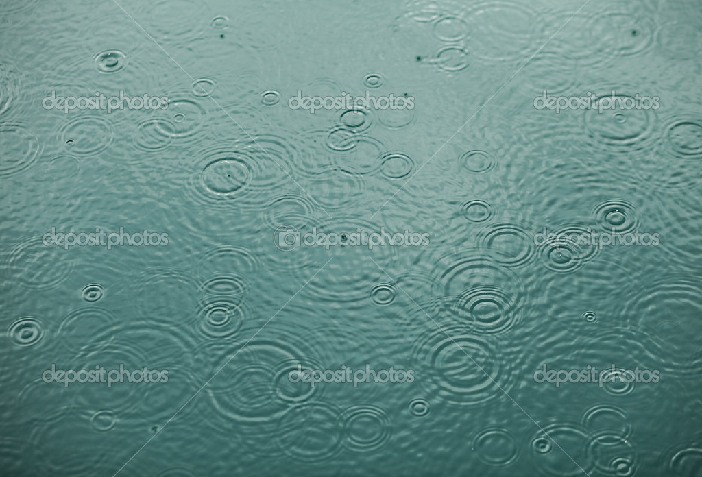 Rain drops falling on clear water. Background photo.