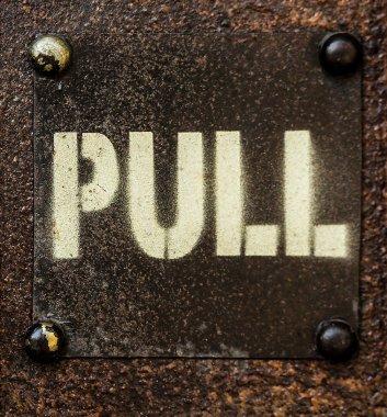 Pull sign on old metal door.