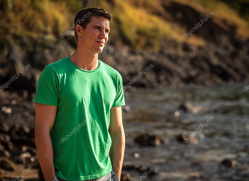 Relaxed attractive man sit on rock near water.