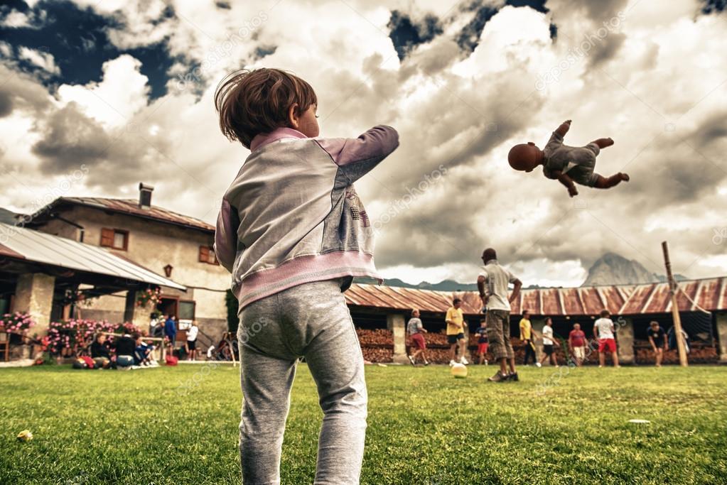 bebé tirando una muñeca en el aire en un parque al aire libre — Foto ...