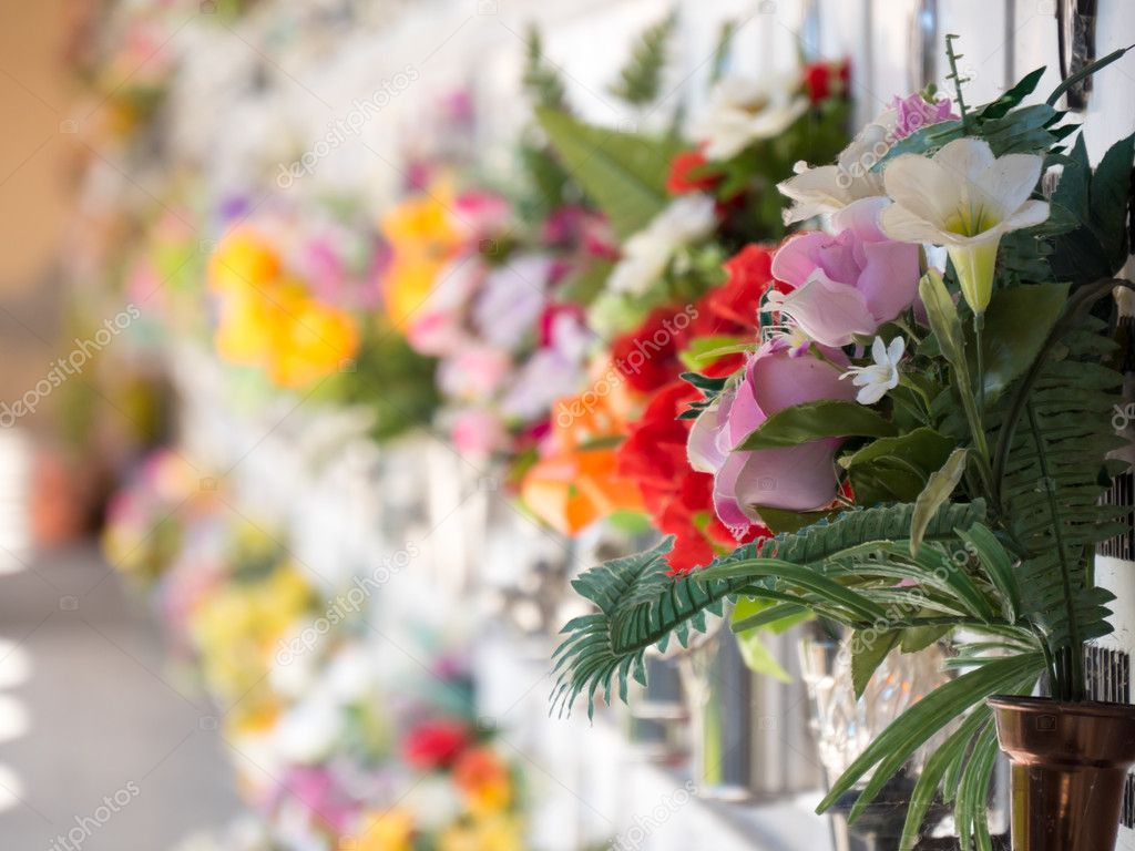 Graves with flowers on a wall of a European cemetery.