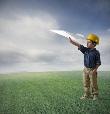 Young boy tries to fly a paper plane