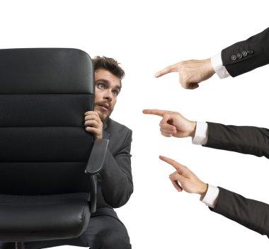 Businessman culprit behind a chair