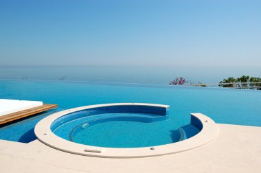 Infinity swimming pool with jacuzzi by beach at the modern luxur