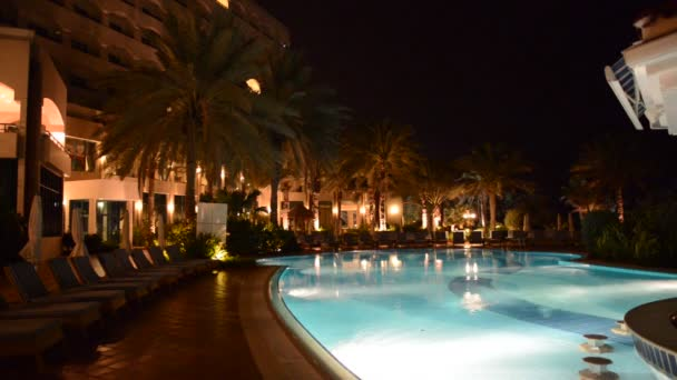 The swimming pool with jacuzzi and bar at luxury hotel in night illumination, Ajman, UAE
