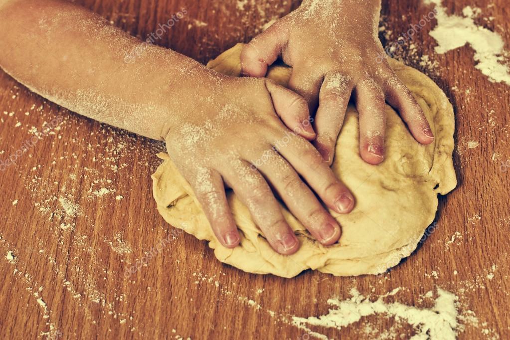 Diligent children hands make a dough.