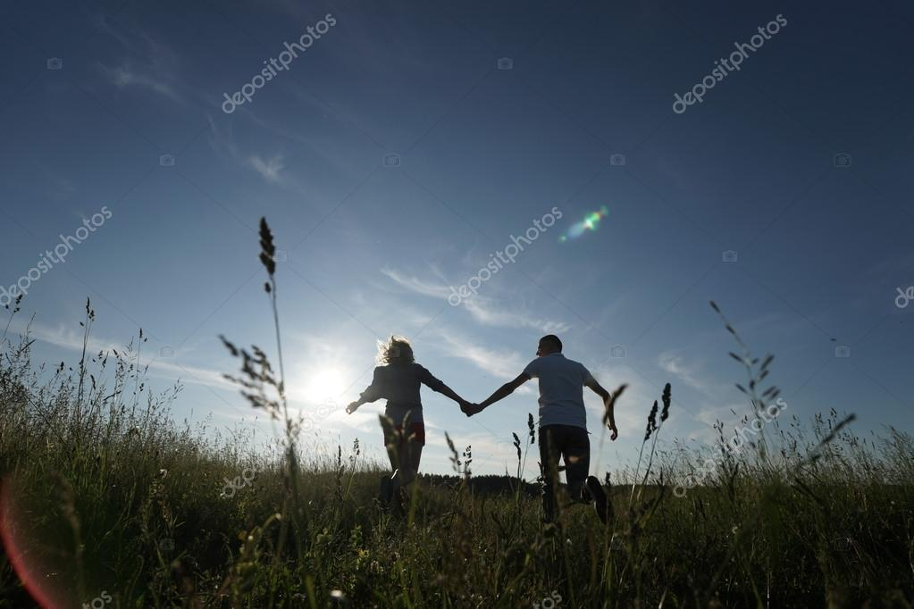Couple walking through field