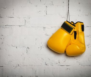 Pair of yellow boxing gloves hanging on a brick wall stock vector