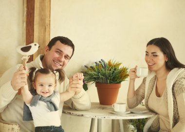 Happy family with one year old baby girl drinking coffee indoor