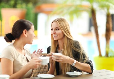 Young women drinking coffee in a cafe outdoors