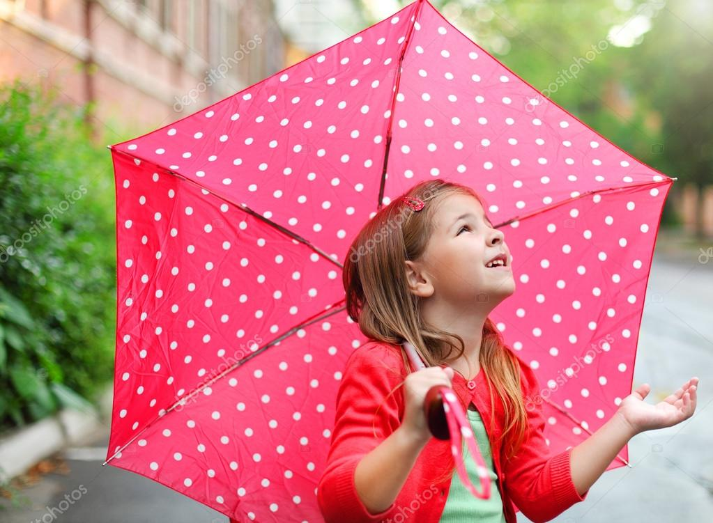 Little girl with polka dots umbrella under the rain