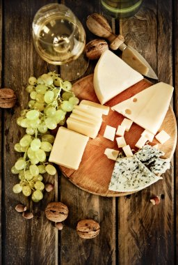 Bottles and glass of white wine, cheese, nuts and grapes