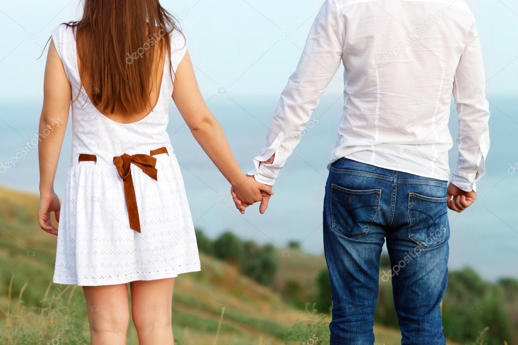 Young couple in love holding hands. Summer sea background