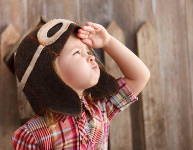 Happy kid playingin pilot helmet near the wooden background stock vector