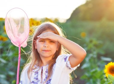 Cheerful little girl playing in a field with insect net