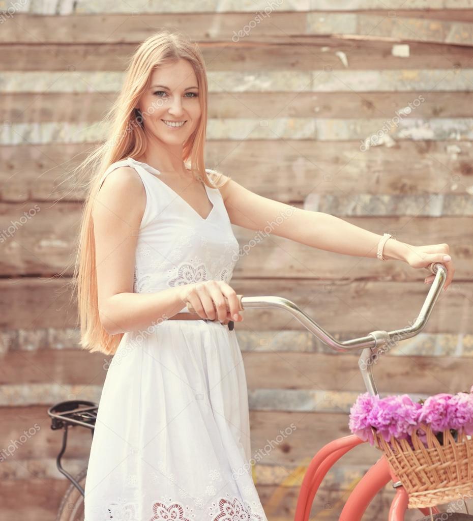 d18d27f9f5 Hermosa mujer rubia con un vestido bonito divirtiéndose en el parque con  bicicleta llevando una hermosa cesta llena de flores de peonía. paisaje  Vintage. ...