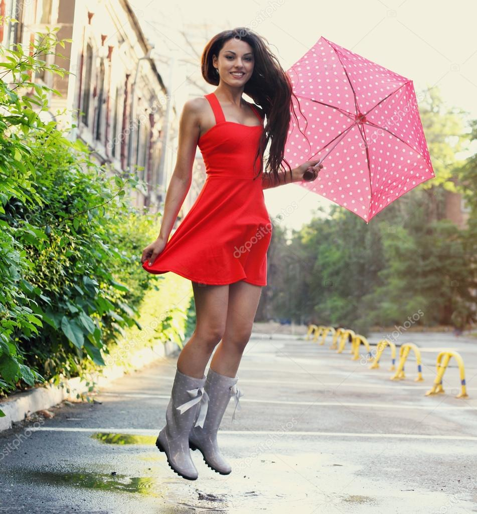 Portrait of beautiful young girl with umbrella under rain