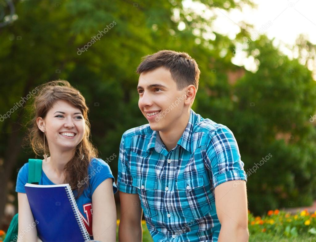 Two students or teenagers with notebooks outdoors