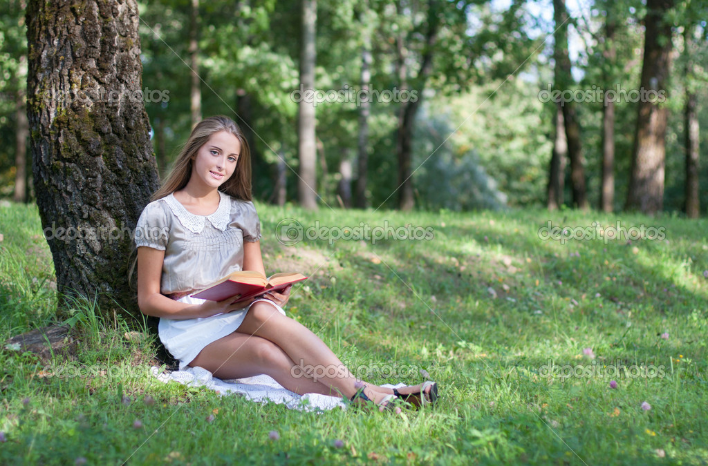 Beautiful girl with book outdoor