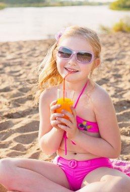 Little girl drinks orange juice outdoor