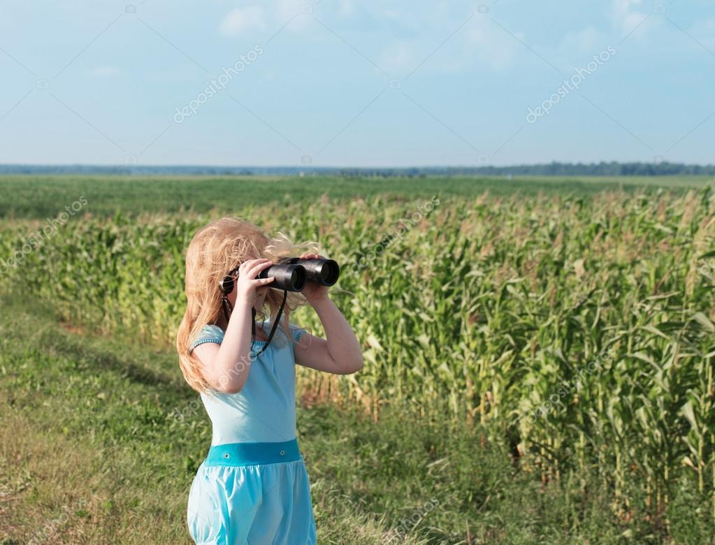 girl looking through binoculars outdoor