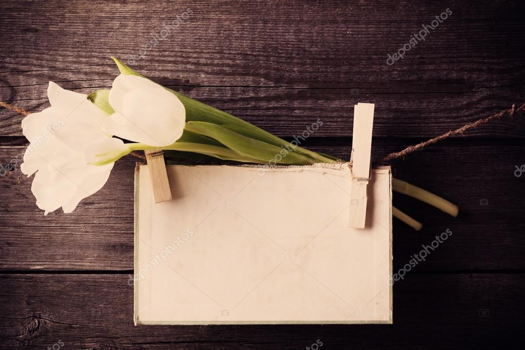 paper attach to rope with clothes pins and tulips  on wooden bac