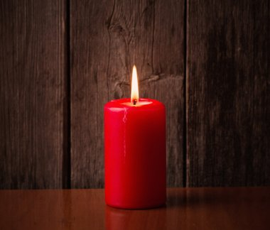 Red candle on wooden background