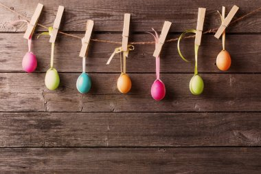 easter eggs attach to rope with clothes pins on wooden backgroun