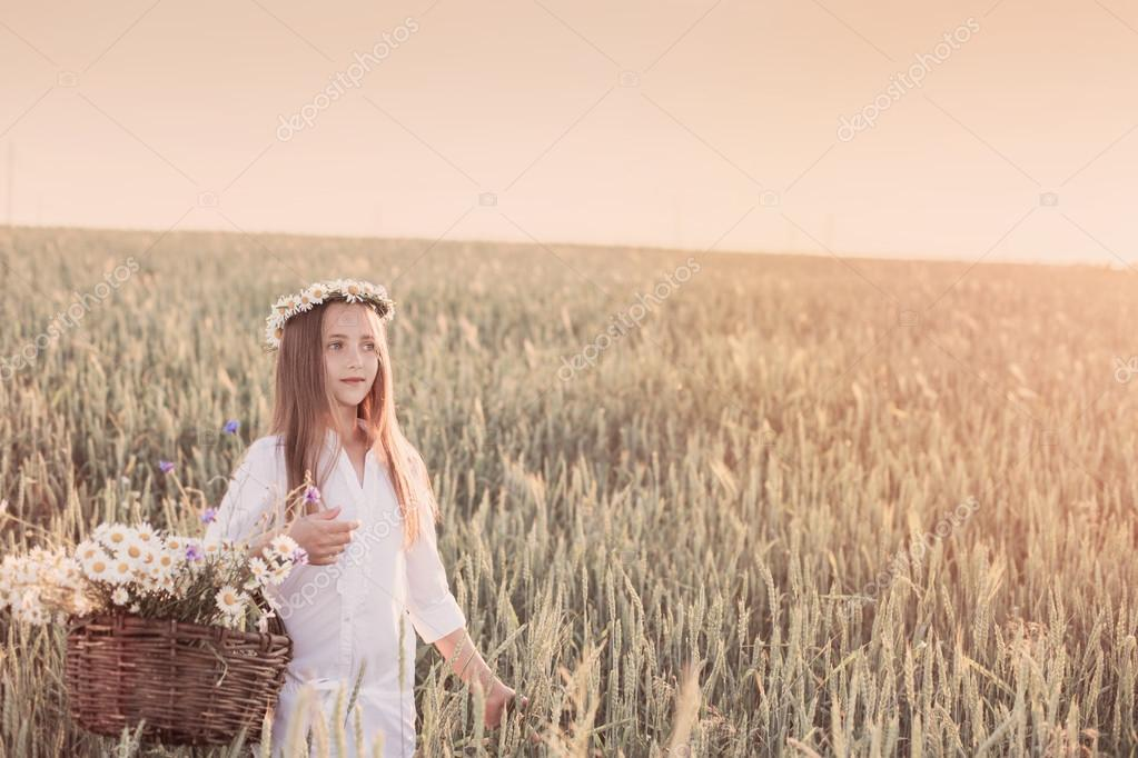 girl in the wheat field with basket of flowers