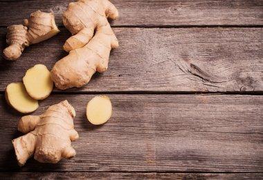 Ginger root sliced on wooden background