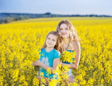 happy women and girl in rape field