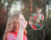 dívka foukání mýdlové bubliny venkovní