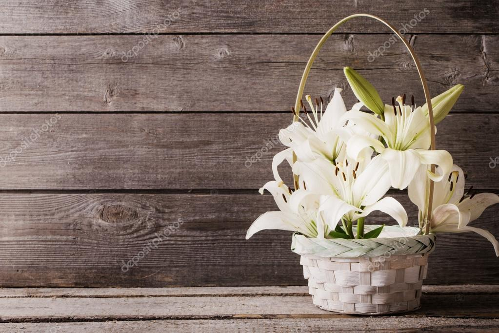 white lily in basket on wooden background
