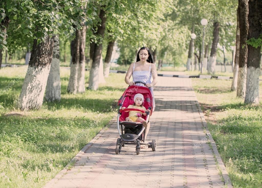 Happy young mother with baby in buggy walking in park