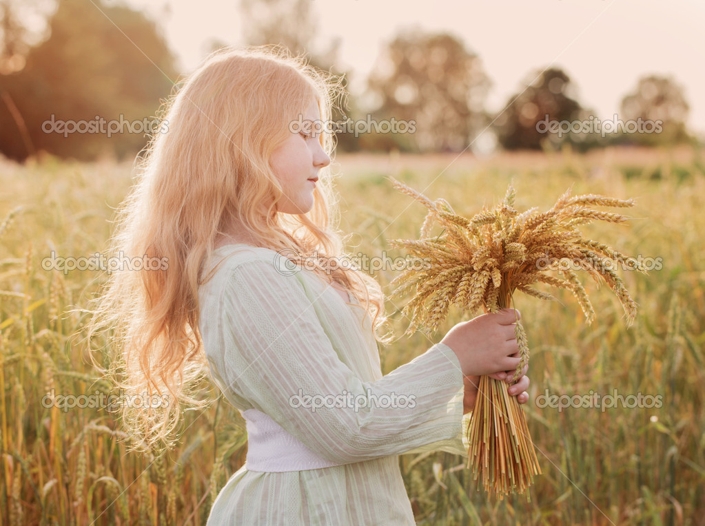 Happy child holding wheat ears at field