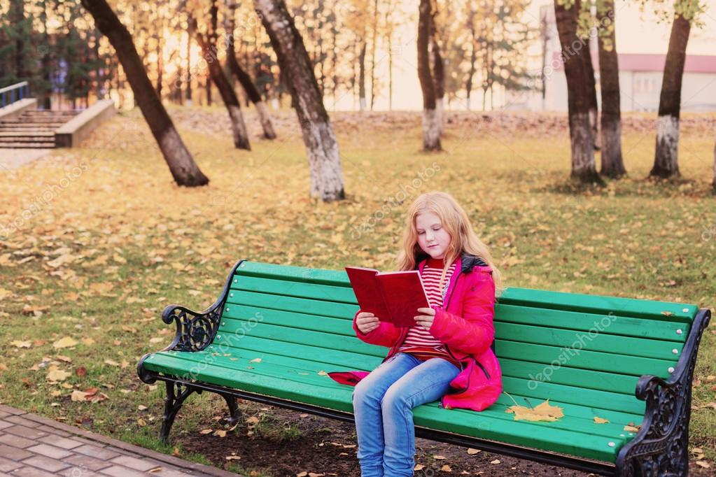 girl with book in autumn park