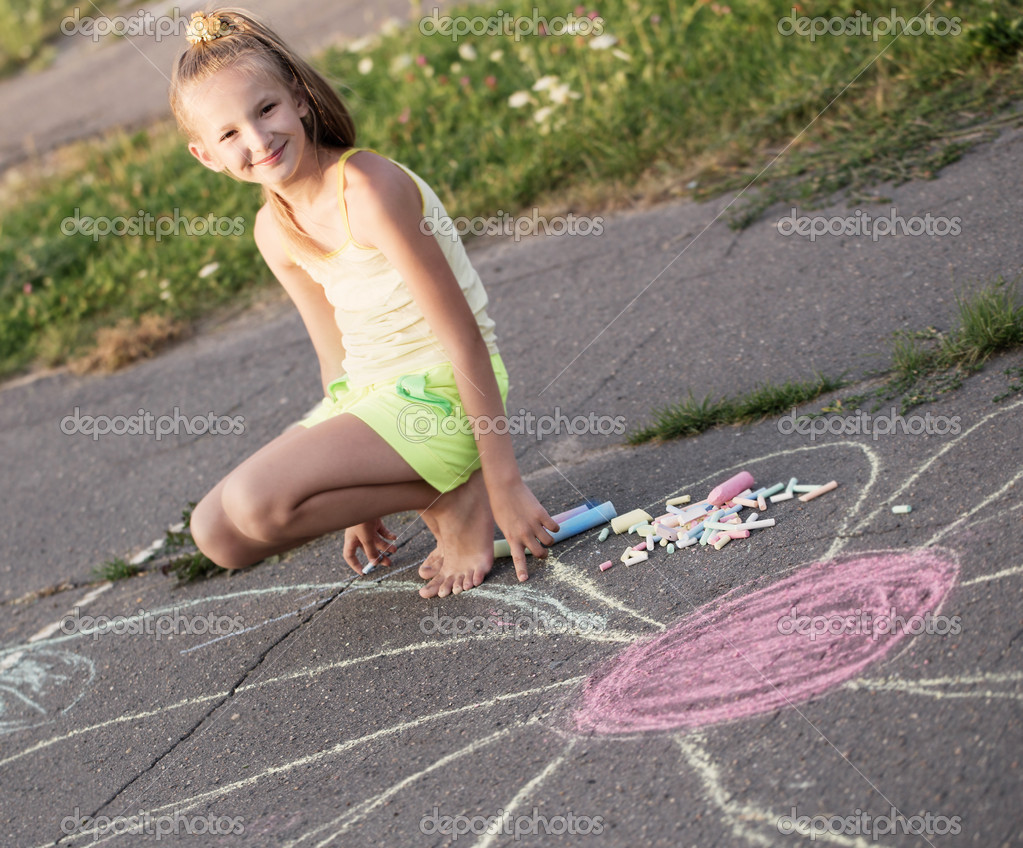The child drawing a chalk on asphalt