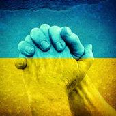 Hände auf ukrainische Flagge