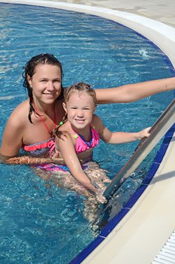 Smiling beautiful woman and her little cute daughter have a fun in pool outdoor