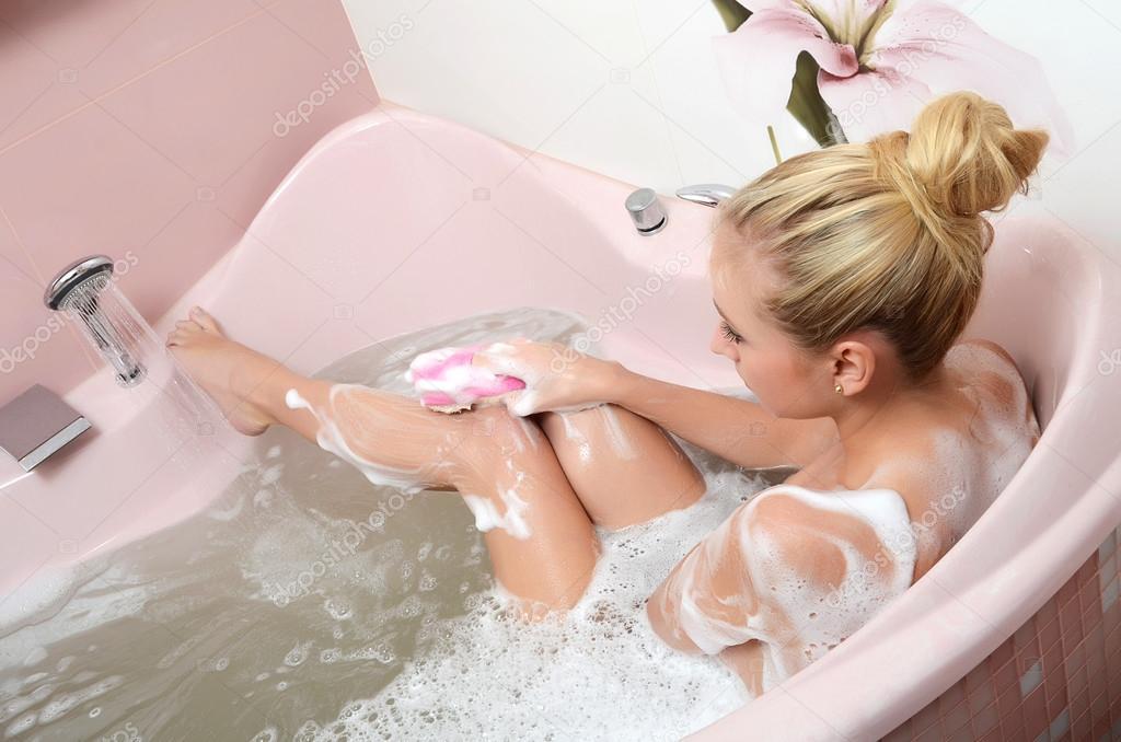 блондинка в пенной ванне бреет ноги