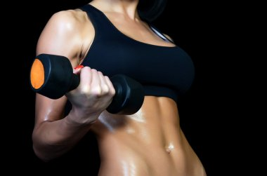 Beautiful brawny body of the woman with dumbbells