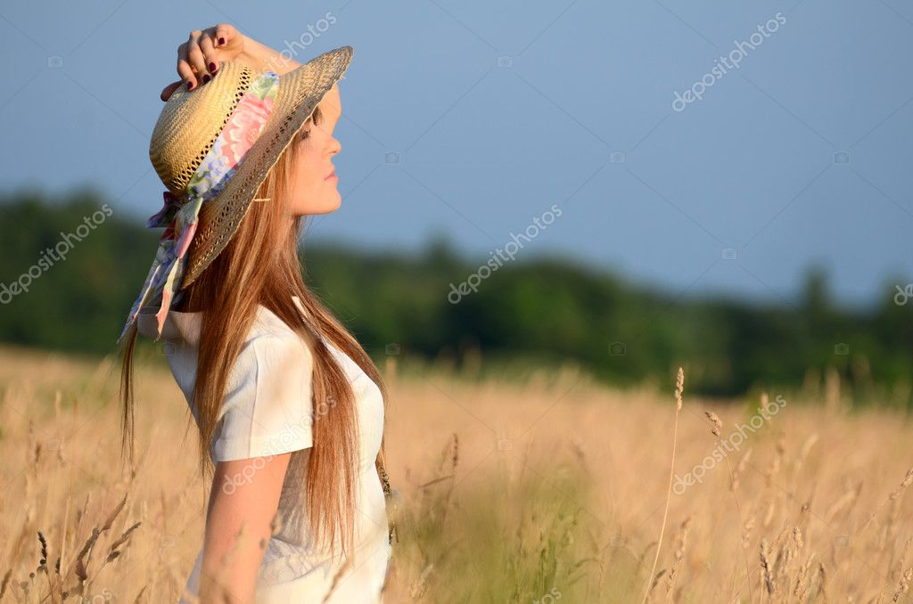 The beautiful woman in a dress in the field