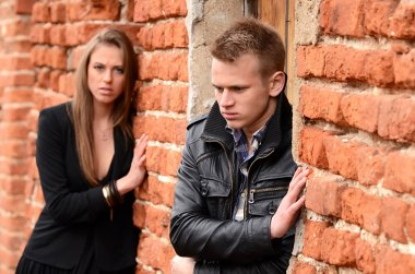 The man and the woman against a brick wall