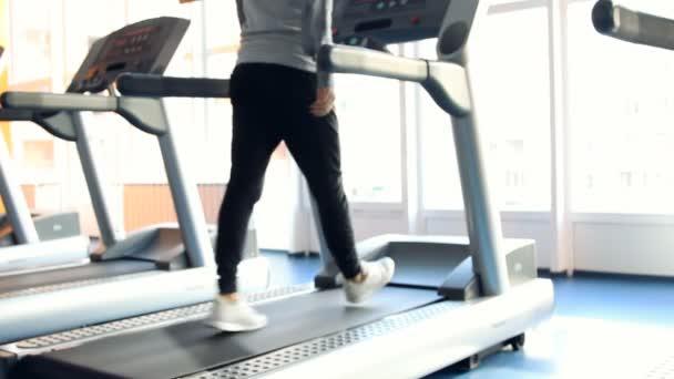 Menschen in der Turnhalle beim Training. laufen auf einer Maschine. Unscharf
