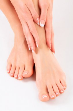 Well-groomed hands on female feet