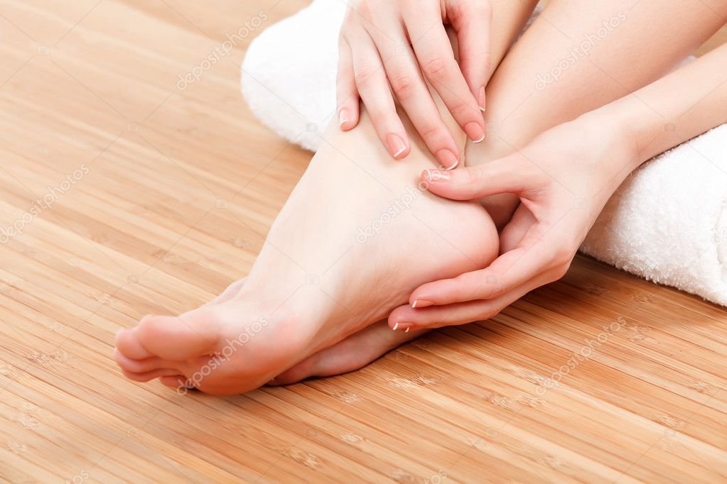 female feet and hands with a white rolled towel